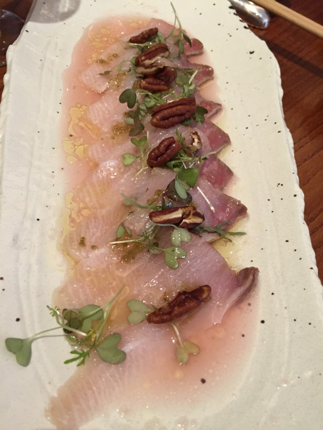 Hamachi with pecan. On top of pickled greens