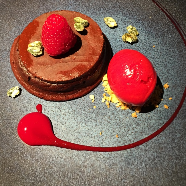 Chocolate fondant with vivid raspberry decoration